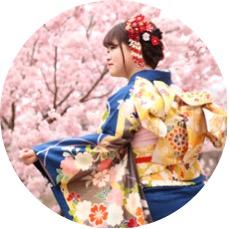 桜の前に立つ振袖姿の女性