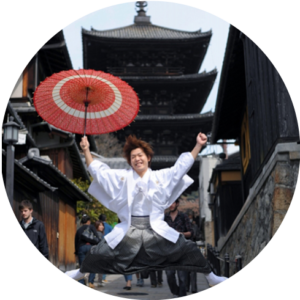 番傘を持ちジャンプをする袴姿の男性