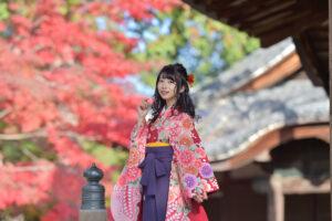 紅葉の前に立つ袴姿の女性