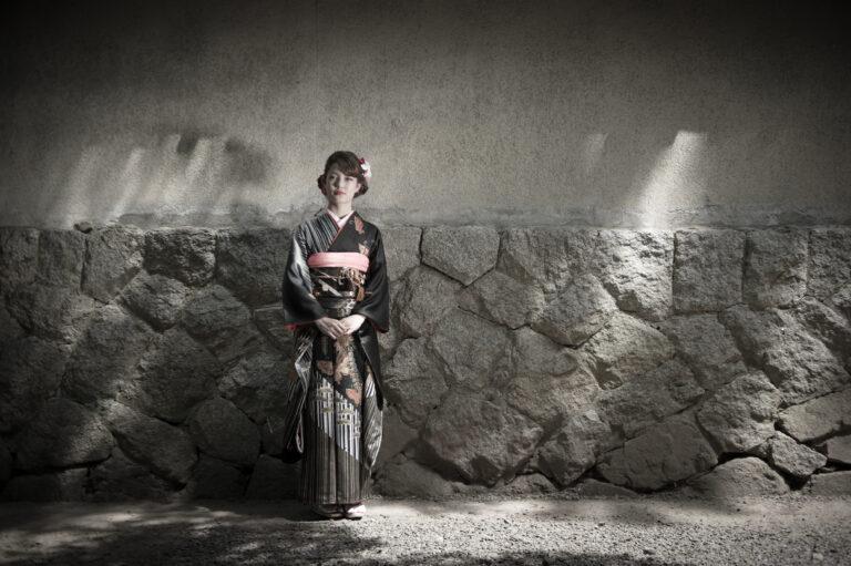 お寺の壁の前で立つ振袖姿の女性
